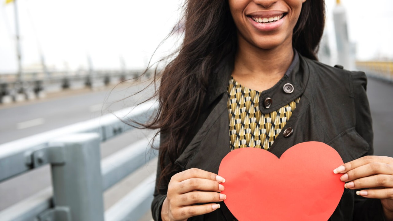 A young woman smiles and holds a red paper heart.