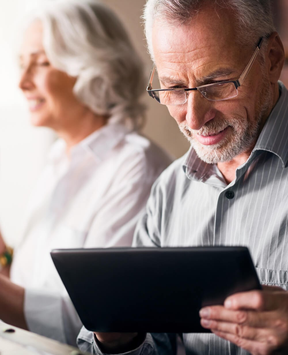 An older couple looks at a tablet computer.