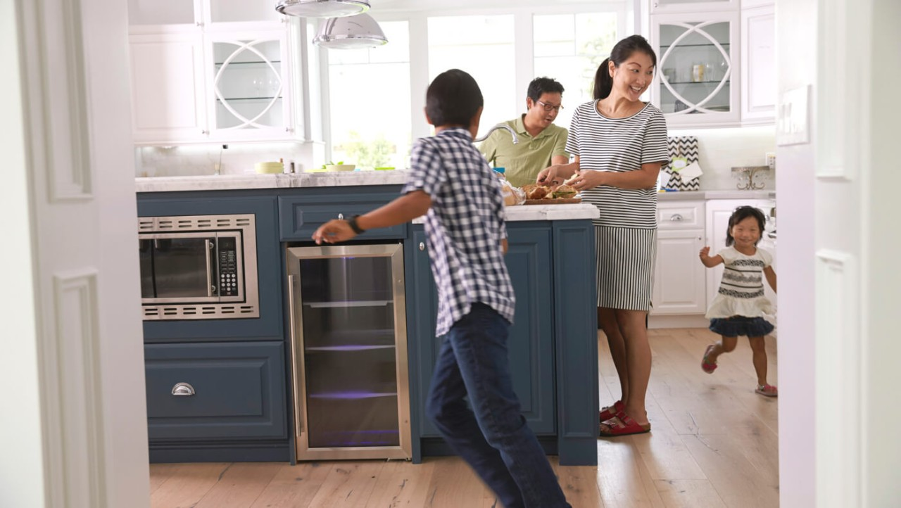 30-something parents watch two young children chase each other in their kitchen.